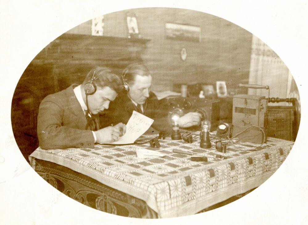 Ansichtspostkarte zweier experimentierender Radiobastler um 1925 Während sich die Männer der Bastelszene in Verbänden zusammenschließen und als fähige Handwerker dargestellt werden, beschränkt sich die Rolle der Frau auf das Zusehen und Mithören. © Museumsstiftung Post und Telekommunikation