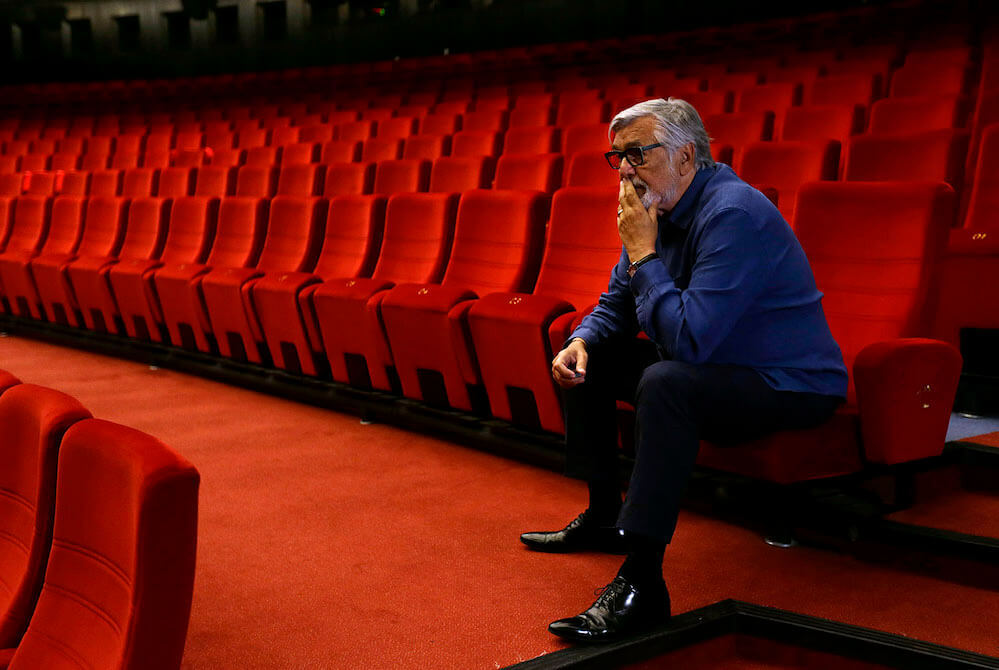 Festival President Jiri Bartoska sits inside an empty cinema before a broadcast of an opening ceremony, as the Karlovy Vary International Film Festival launches a nationwide programme to bring its films to cinemas around the country after cancelling its main events following the coronavirus disease (COVID-19) outbreak in Karlovy Vary, Czech Republic, July 3, 2020.  REUTERS/David W Cerny